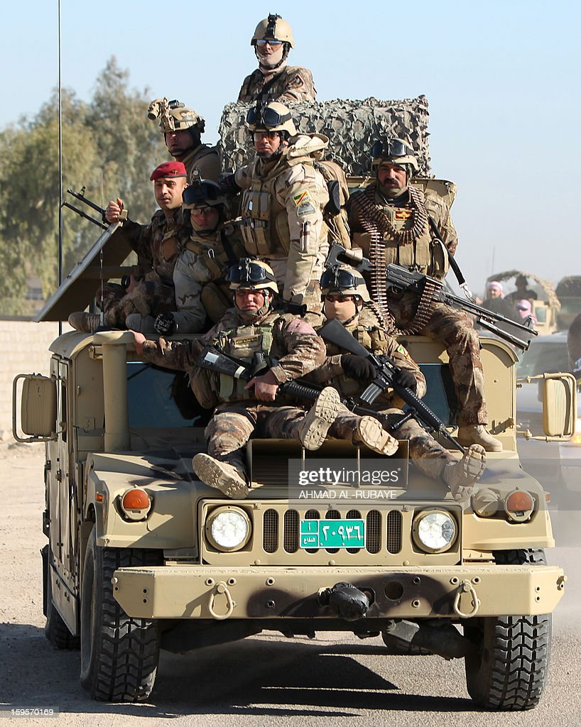 Iraqi soldiers crowd on an armoured vehicle as they protect the road to the cemetery during the funeral procession of MP Ayfan Saadun al-Essawi, of the secular Sunni-backed Iraqiya bloc, as it takes place in the western town of Fallujah, 50 kilometers from Baghdad, on January 16, 2013, in Anbar province. Essawi, 37-years-old, was killed by a suicide bomber who wrapped his arms around the lawmaker before blowing himself up, as a political crisis engulfed Iraq.