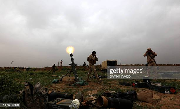 Iraqi soldiers fire mortar shells as they hold a position on the outskirts of Makhmur about 280 kilometres north of the capital Baghdad on March 26...