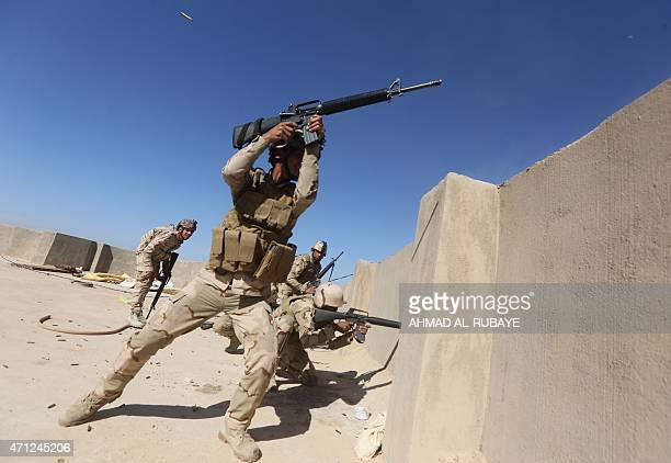 Iraqi soldiers fire their weapons towards Islamic State group positions in the Garma district west of the Iraqi capital Baghdad on April 26 where...