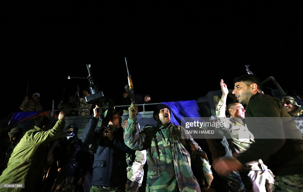 Iraqi army members flash their weapons as they prepare to head towards Makhmur, about 280 kilometres (175 miles) north of the capital Baghdad, on February 11, 2016. The Iraqi army is deploying thousands of soldiers to a northern base in preparation for operations to retake the Islamic State (IS) group's hub of Mosul, according to officials, as IS still holds Fallujah, east of Ramadi, and Mosul, Iraq's second city that is located in the north. / AFP / SAFIN HAMED