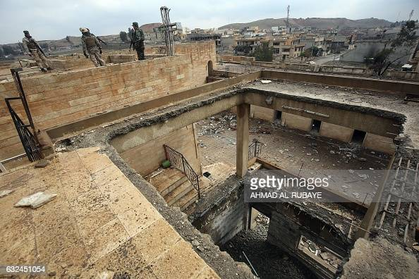 TOPSHOT Iraqi soldiers inspect the debris on January 22 2017 at St George's Monastery a historical Chaldean Catholic church on the northern outskirt...