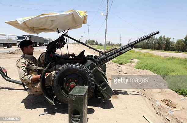 Iraqi soldiers man an antiaircraft gun in the central city of Karbala on June 14 to prepare for any militant offensive Shiite Iran offered to...