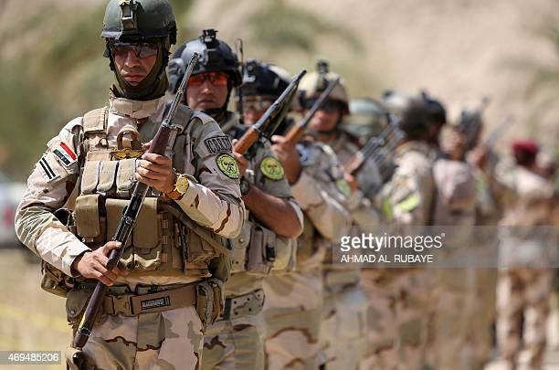 Iraqi soldiers march during a ceremony at the site of a mass grave containing the remains of people believed to have been slain by jihadists of the...