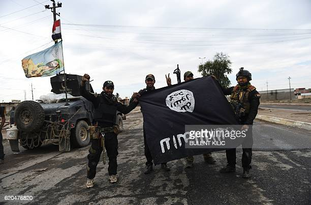 TOPSHOT Iraqi soldiers pose with an Islamic State group flag as they hold a position in the village of Gogjali a few hundred metres of Mosul's...