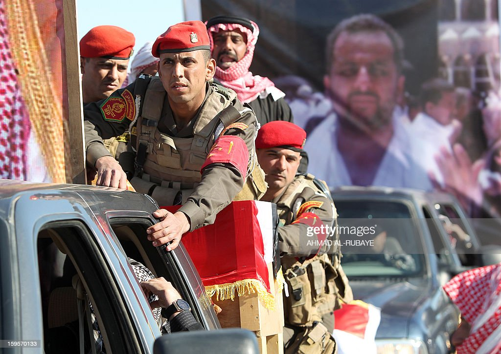 Iraqi soldiers ride on the back of a truck carrying the coffin of MP Ayfan Saadun al-Essawi, of the secular Sunni-backed Iraqiya bloc, during his funeral in the western town of Fallujah, 50 kilometers from Baghdad, on January 16, 2013, in Anbar province. Essawi, 37-years-old, was killed by a suicide bomber who wrapped his arms around the lawmaker before blowing himself up, as a political crisis engulfed Iraq.