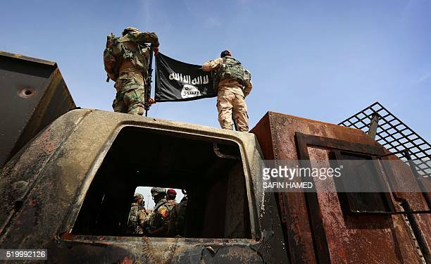 Iraqi soldiers show a flag that they seized from the Islamic State group as they hold a position near the frontline on April 9 2016 in the town of...