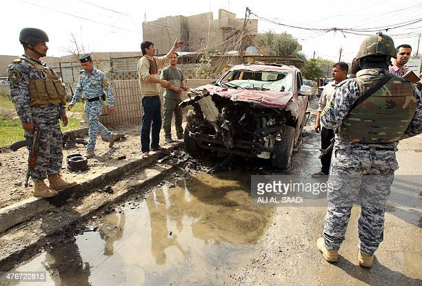 Iraqi soldiers stand guard as civilians inspect the site of a car bomb explosion in central Baghdad on March 5 2014 Nine bombings mainly targeting...