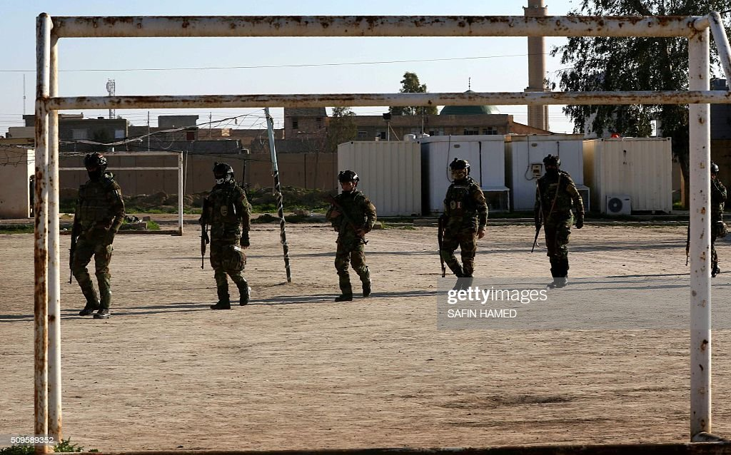 Iraqi army members stand guard at the entrance of the Nineveh base for liberation operations in Makhmur, about 280 kilometres (175 miles) north of the capital Baghdad, on February 11, 2016. The Iraqi army is deploying thousands of soldiers to a northern base in preparation for operations to retake the Islamic State (IS) group's hub of Mosul, according to officials, as IS still holds Fallujah, east of Ramadi, and Mosul, Iraq's second city that is located in the north. / AFP / SAFIN HAMED