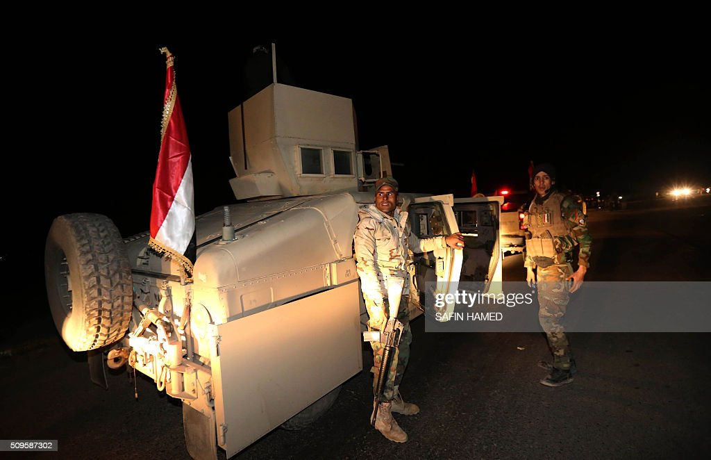 Iraqi army members stand next to armoured vehicles as they head towards Makhmur, about 280 kilometres (175 miles) north of the capital Baghdad, on February 11, 2016. The Iraqi army is deploying thousands of soldiers to a northern base in preparation for operations to retake the Islamic State (IS) group's hub of Mosul, according to officials, as IS still holds Fallujah, east of Ramadi, and Mosul, Iraq's second city that is located in the north. / AFP / SAFIN HAMED