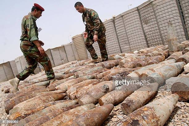 Iraqi soldiers walk among munitions recovered from a weapons cache in the southern city of Amara in Maysan province 365 kilometers south of Baghdad...