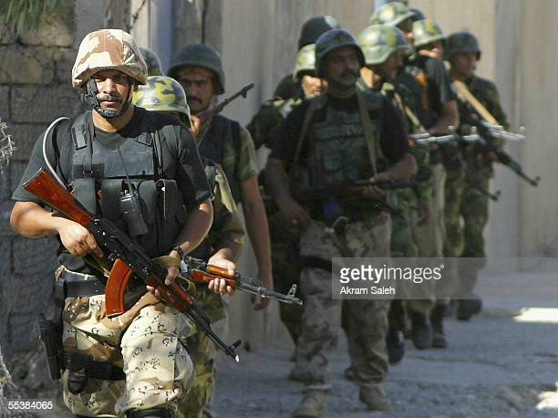 Iraqi soldiers walk as they conduct housetohouse searches September 12 2005 in Tall Afar 93 miles east the Syrian border 260 miles northwest of...