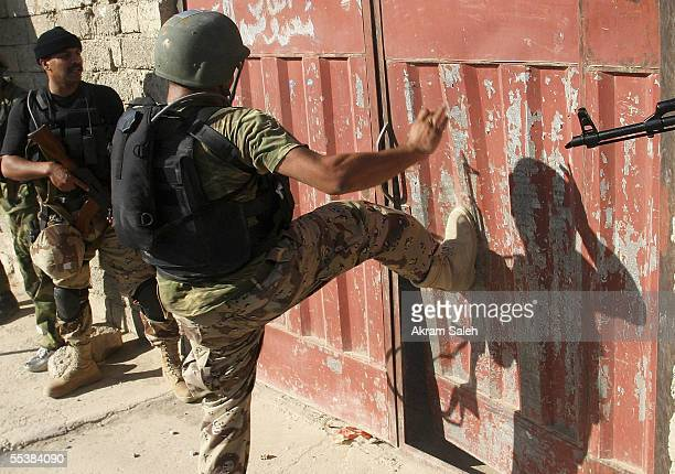 Iraqi soliders open a house gate as they conduct housetohouse searches September 12 2005 in Tall Afar 93 miles east the Syrian border 260 miles...