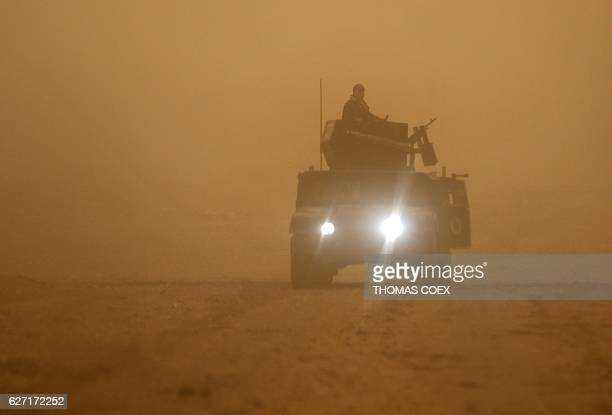 Iraqi Special Forces drive an armoured vehicle in an eastern district of Mosul during a heavy dust storm on December 2 during a broad offencive by...