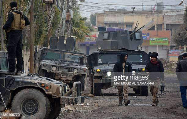 Iraqi special forces gather next to their armoured vehicles in the neighbourhood of alBarid east of Mosul on December 18 2016 during their ongoing...