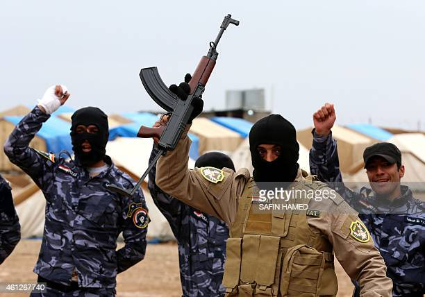 Iraqi special forces policemen cheer as they line up during a training session at a camp in the Bardarash district 30 kilometres northeast of Mosul...