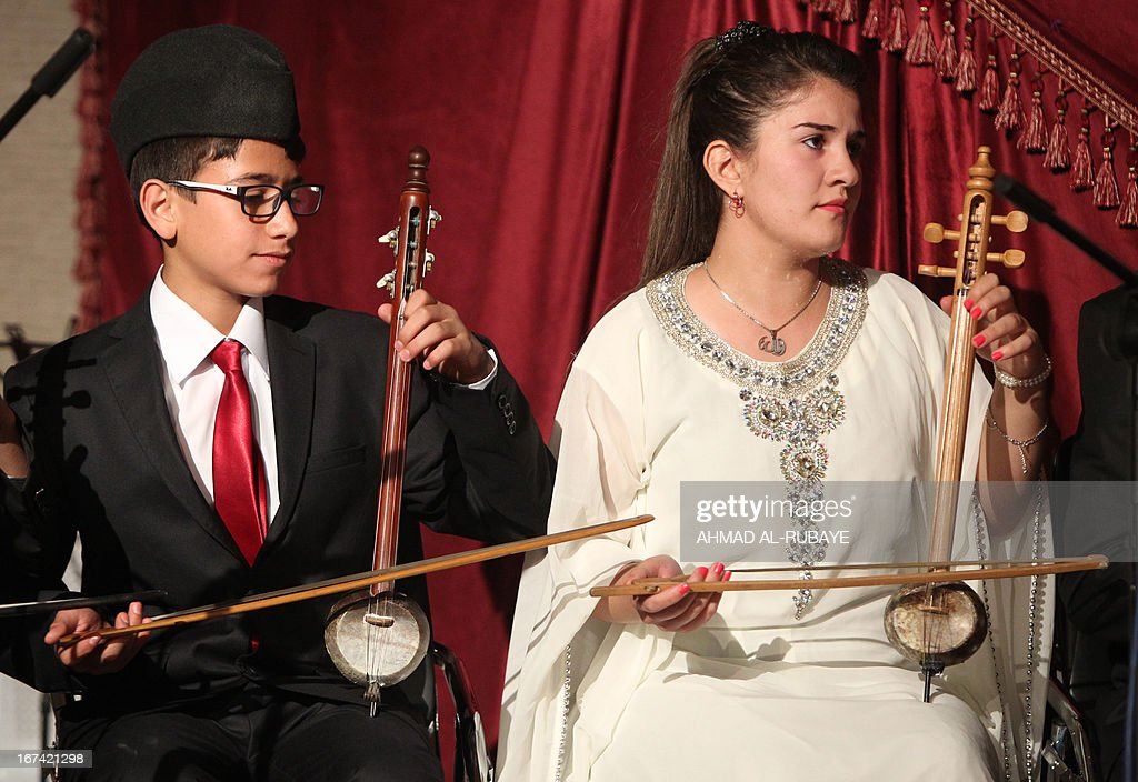 Iraqi students from the ballet and music school, play the traditional 2-stringed bowed instrument, the rebab, as they perform during their annual production that marks the end of the school year, at al-Ribat hall theatre in central Baghdad on April 25, 2013.