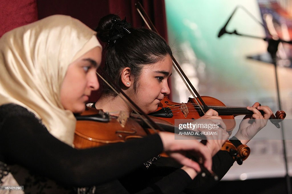 Iraqi students from the ballet and music school, play the violin as they perform during their annual production that marks the end of the school year, at al-Ribat hall theatre in central Baghdad on April 25, 2013.