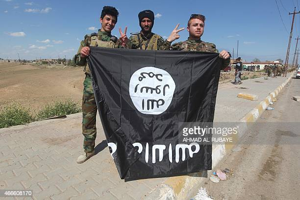 Iraqi Sunni and Shiite fighters pose for a photo with an Islamic State group flag in the AlAlam town northeast of the Iraqi city of Tikrit on March...