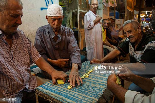 Iraqi Sunni men play dominos at a small coffee shop in the Adhamiyah neighborhood of Baghdad Iraq The men all taxi drivers say they recently began to...