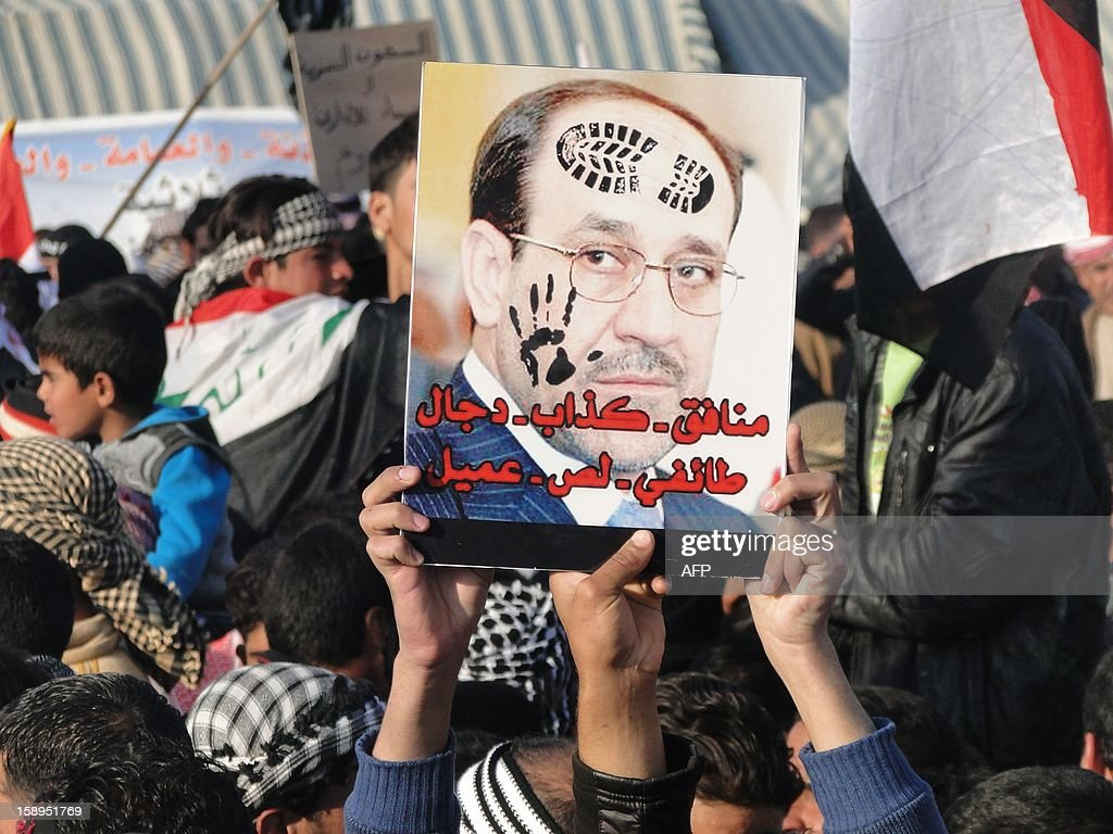 Iraqi Sunni protestors hold up a portrait of Prime Minister Nuri al-Maliki with slogans reading in Arabic, 'liar...sectarian, thief, collaborator' during a protest against him on the main highway to Syria and Jordan near Ramadi, Anbar's provincial capital west of Baghdad, on January 4, 2012. Thousands of Sunnis demonstrated across Iraq on Friday, in the latest of nearly two weeks of rallies criticising the country's premier and demanding the release of prisoners they say are wrongfully held.