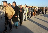 Iraqi Sunni volunteers stand in line at the AlAsad air base in Iraq's mainly Sunni Anbar province on November 11 2014 before they start to be trained...