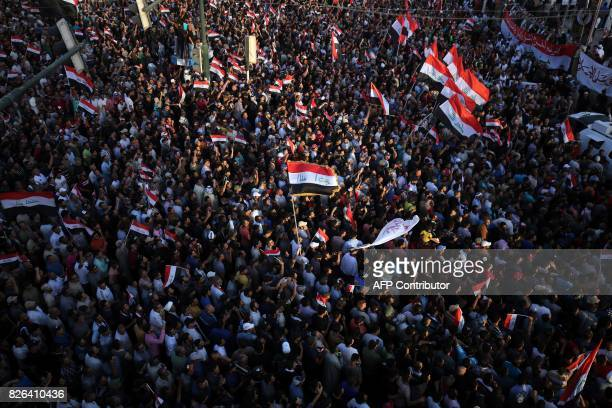 TOPSHOT Iraqi supporters of cleric Moqtada alSadr wave their national flags and shout slogans during a demonstration in Tahrir Square central Baghdad...