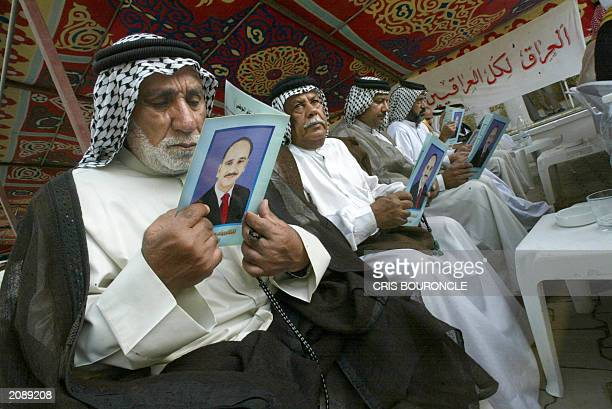 Iraqi sympathizers to the Constitutional Monarchy Movement read pamphlets emblazoned with the portrait of AlShareef Ali bin alHussein a pretender to...
