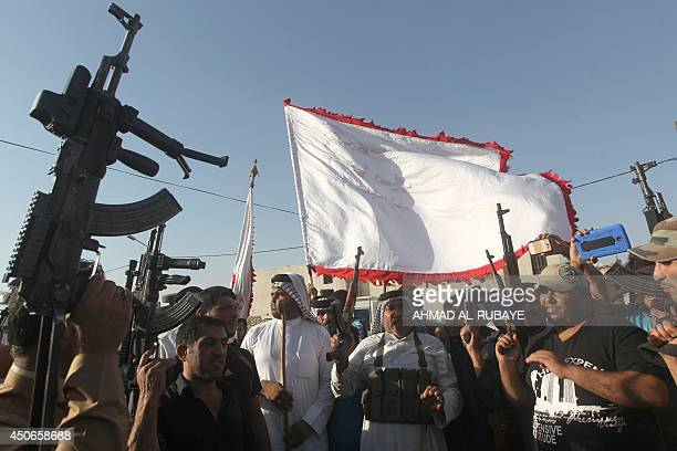 Iraqi tribes men carry their weapons as they gather volunteering to fight along side the Iraqi security forces against Jihadist militants who have...