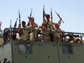 Iraqi troops aboard military vehicles raise up their weapons as they arrive to support the Sunni antiAlQaeda militia Sahwa in its fight against...