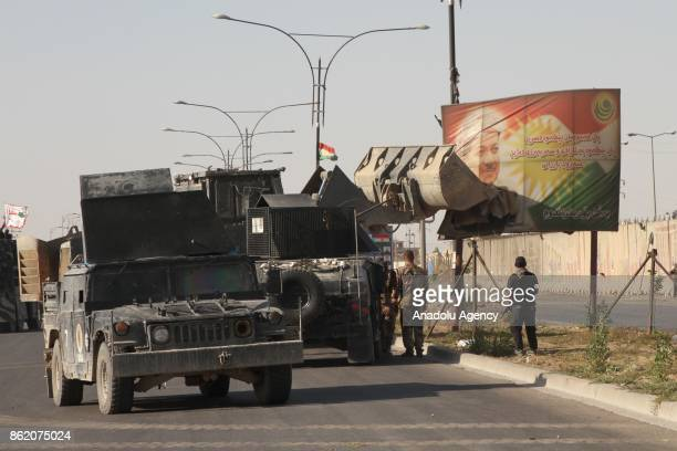 Iraqi troops demolish a billboard depicting Iraqi Kuridish Regional Government President Masoud Barzani's portrait after Iraqi soldiers retook the...