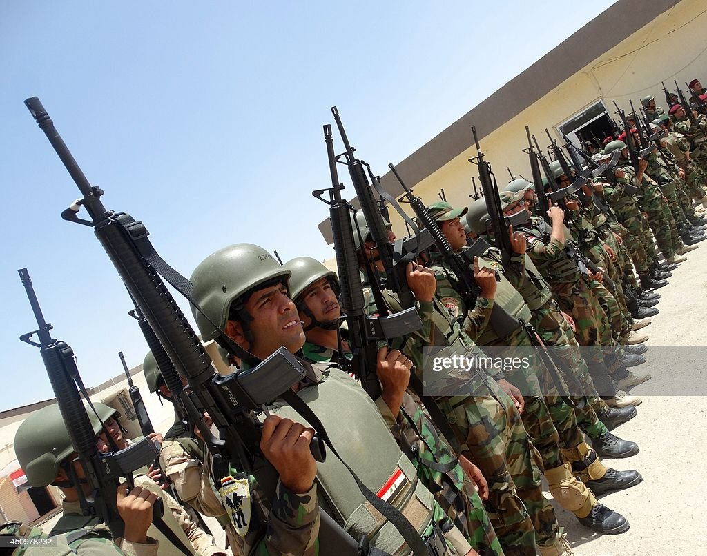 Iraqi troops stand in rows holding their weapons as they arrive to support the Sunni antiAlQaeda militia Sahwa in its fight against antigovernment...