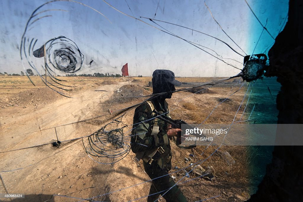 Iraqi Turkmen forces patrol a checkpoint in the northern town of Taza Khormato 20 kms south of Kirkuk on June 21 close to locations of jihadist...