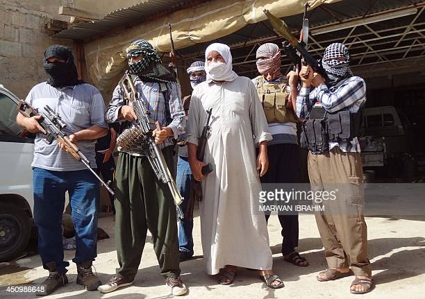 Iraqi Turkmen pose with their weapons as they get ready to fight against militants led by the jihadist Islamic State of Iraq and the Levant on June...