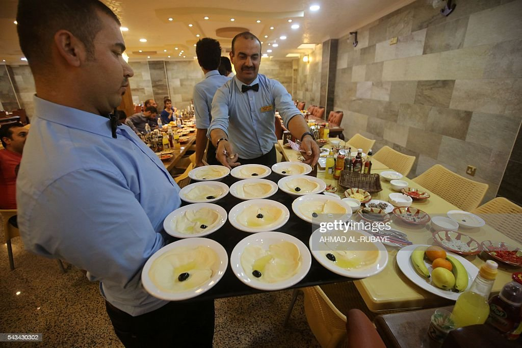 Iraqi waiters work at a restaurant where customers come to break the fast with an Iftar diner during the Muslim feating month of ramadan on June 28, 2016 in the capital Baghdad. / AFP / AHMAD