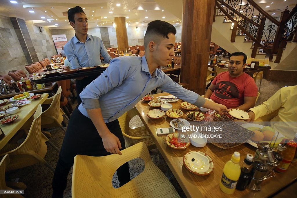 An Iraqi waiter serves customers who break the fast with an Iftar diner at a restaurant during the Muslim feating month of ramadan on June 28, 2016 in the capital Baghdad. / AFP / AHMAD