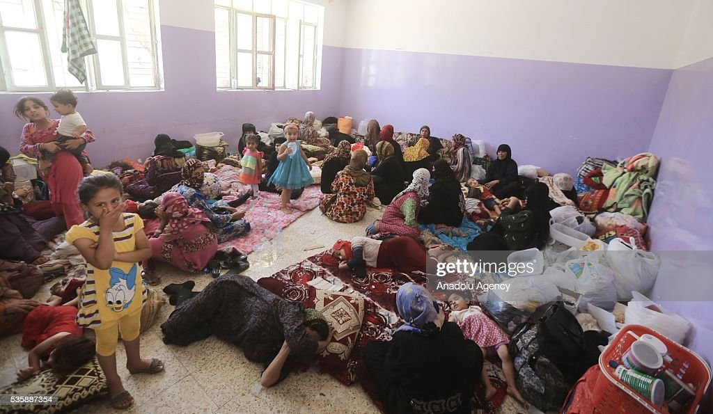 Iraqi woman and children sleep on a carpet and ground as they leave their home in Fallujah town due to conflicts between Daesh and security forces in Anbar, Iraq on May 30, 2016. Some of the families who left their home are placed in a school in Karma Town, west of Anbar city.