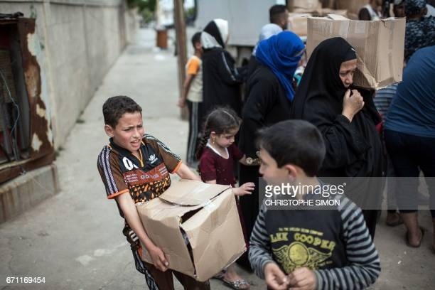 Iraqi women and children in west Mosul receive aid packages given by volunteers from the eastern side on April 21 as Iraqi forces continue the...