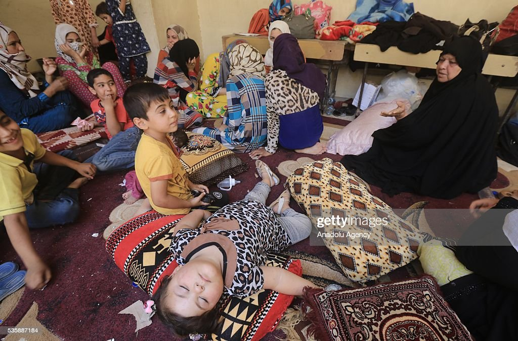 Iraqi women and children sit inside a classroom as they leave their home in Fallujah town due to conflicts between Daesh and security forces in Anbar, Iraq on May 30, 2016. Some of the families who left their home are placed in a school in Karma Town, west of Anbar city.