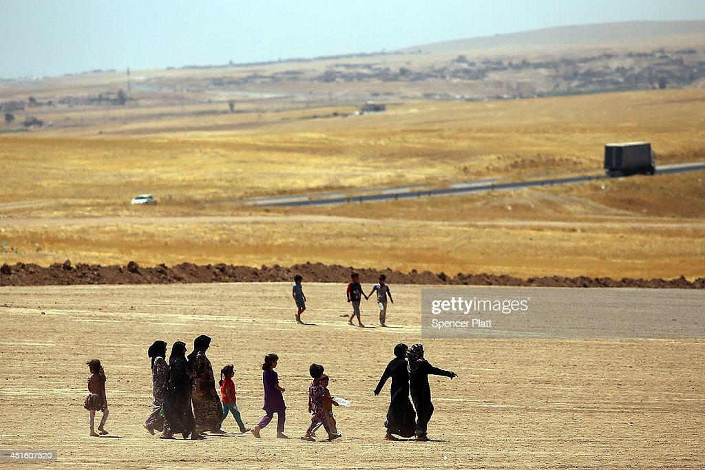 Iraqi women and children walk towards a camp entrance as thousands of Iraqis who have fled recent fighting in the cities of Mosul and Tal Afar try to enter a temporary displacement camp but are blocked by Kurdish soldiers on July 2, 2014 in Khazair, Iraq. The families, many with small and sick children, have no shelter and little water and food. The displacement camp Khazair is now home to an estimated 1,500 internally displaced persons (IDP's) with the number rising daily. Tens of thousands of people have fled Iraq's second largest city of Mosul after it was overrun by ISIS (Islamic State of Iraq and Syria) militants. Many have been temporarily housed at various IDP camps around the region including the area close to Erbil, as they hope to enter the safety of the nearby Kurdish region.