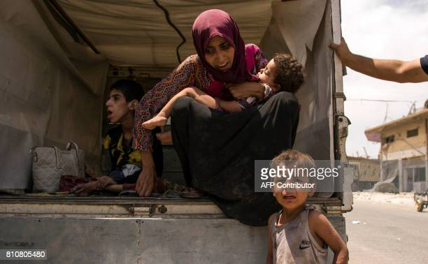 Iraqi women and children who fled the fighting between government forces and Islamic State group jihadists in the Old City of Mosul sit in a vehicle...