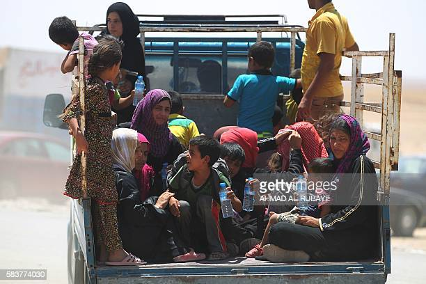 TOPSHOT Iraqi women and children who fled the towns of alShirqat and Qayyarah during reported fighting between Iraqi government forces and jihadists...