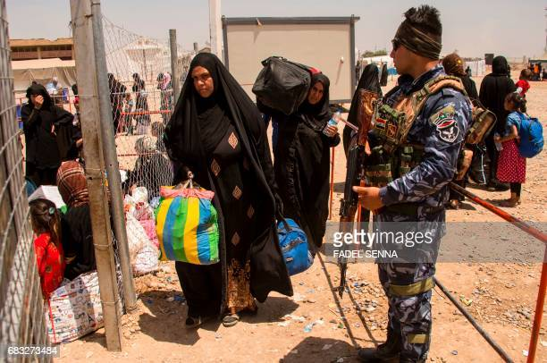 Iraqi women arrive at a camp for internally displaced people in Hammam alAlil on May 14 after fleeing west Mosul due to the government forces ongoing...