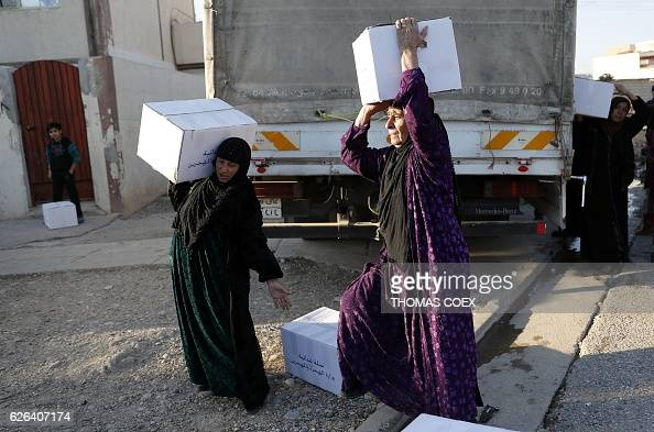 Iraqi women carry boxes of food aid distributed by the Iraqi ministry of migrants and refugees in a central district of Mosul on November 29 during...
