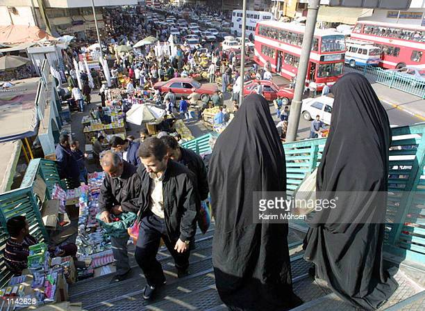 Iraqi women carry food from a supermarket during Islam's holy month of Ramadan November 25 2001 in Baghdad Iraq Iraq said it would reject a...