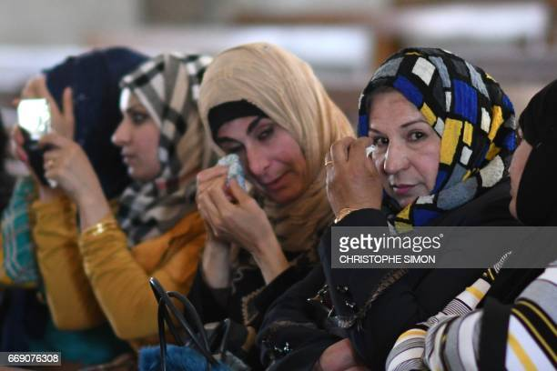 Iraqi women cry as they attend an easter procession at the Saint John's church in the nearly deserted predominantly Christian Iraqi town of Qaraqosh...