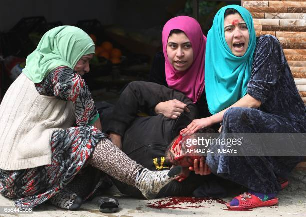 TOPSHOT Iraqi women cry over their brother's body who was killed by a mortar shell fired by Islamic State group jihadists on civilians who were...