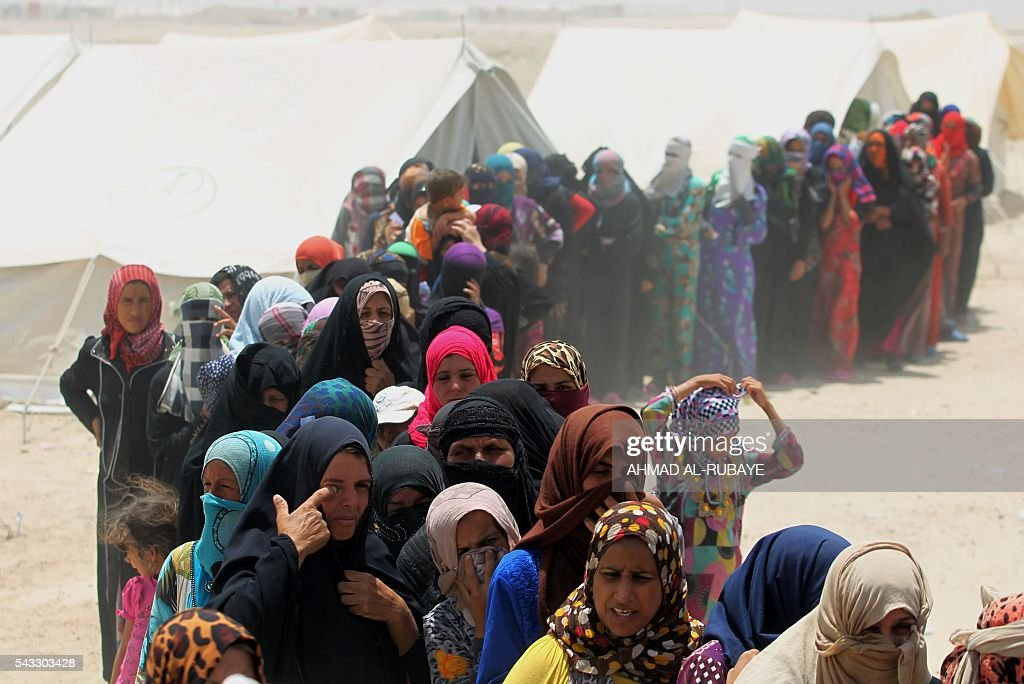 Iraqis women displaced from the city of Fallujah queue up to collect aid distributed by the Norwegian Refugee Council at a newly opened camp where they are taking shelter in Amriyat al-Fallujah on June 27, 2016, south of Fallujah. Iraqi forces on June 26 wrapped up operations in Fallujah and declared the area free of jihadists from the Islamic State (IS) group after a month-long operation. The government said the destruction caused by the fighting was limited and vowed to do its utmost to allow the tens of thousands of displaced civilians to return to their homes. RUBAYE