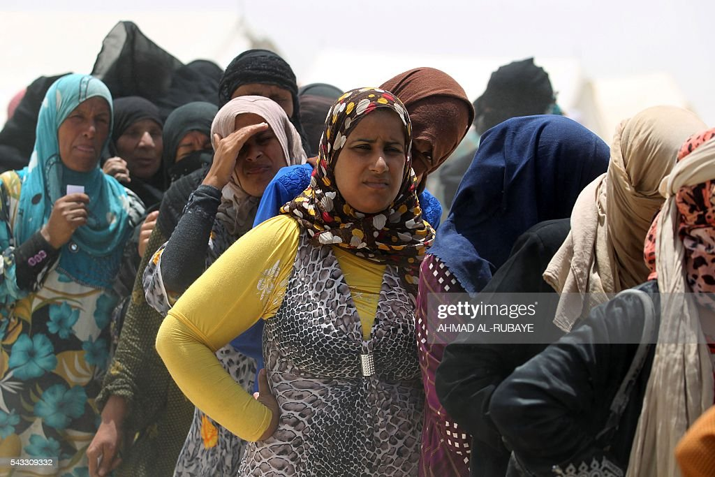 Iraqi women displaced from the city of Fallujah queue up to collect aid distributed by the Norwegian Refugee Council at a newly opened camp where they are taking shelter in Amriyat al-Fallujah on June 27, 2016, south of Fallujah. Iraqi forces on June 26 wrapped up operations in Fallujah and declared the area free of jihadists from the Islamic State (IS) group after a month-long operation. The government said the destruction caused by the fighting was limited and vowed to do its utmost to allow the tens of thousands of displaced civilians to return to their homes. RUBAYE