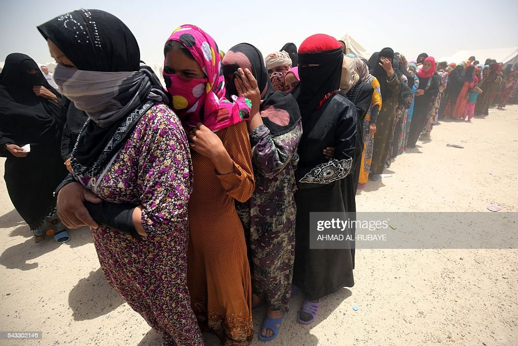 Iraqi women displaced from the city of Fallujah wait to receive aid distributed by the Norwegian Refugee Council at a makeshift camp where they are taking shelter in Amriyat al-Fallujah on June 27, 2016. Iraqi forces on June 26 wrapped up operations in Fallujah and declared the area free of jihadists from the Islamic State (IS) group after a month-long operation. The government said the destruction caused by the fighting was limited and vowed to do its utmost to allow the tens of thousands of displaced civilians to return to their homes. RUBAYE