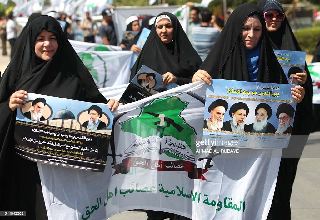 Iraqi women hold placards depicting portraits of (R to L) Iran's supreme leader Ayatollah Ali Khamenei, Grand Ayatollah Ali Sistani, former Iraqi Shiite cleric Muhammad Baqir al-Sadr and late revolutionary leader Ayatollah Ruhollah Khomeini, as they take part in a parade marking al-Quds (Jerusalem) Day in the capital Baghdad, on July 1, 2016. RUBAYE